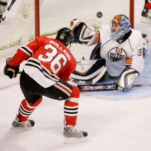 Dave Bolland knocks in a puck over Edmonton goalie Dwayne Roloson.