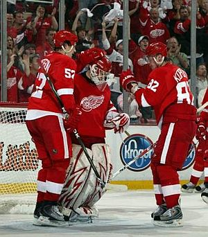 Detroit Red Wings Jonathan Ericsson and Tomas Kopecky congratulate goalie Chris Osgood aftger his 4-0 shutout win over Columbus in game 2 on Saturday April 18. (JULIAN H. GONZALEZ/DFP)