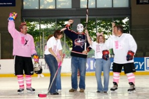 "Matt ""Jason"" Garrett drops the ceremonial first puck between Alison Lukan (left) and Anna Cluxton (right)/Photo courtesy of Rachel Lewis"