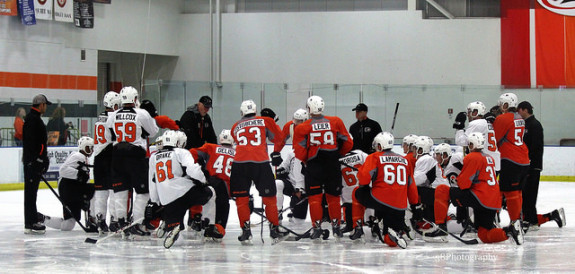 Flyers prospect huddle around the coach at development camp. [Photo: Amy Irvin]
