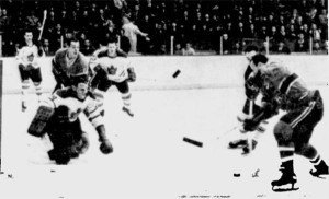 Terry Sawchuk stops Claude Provost in action from last night's game in Montreal.