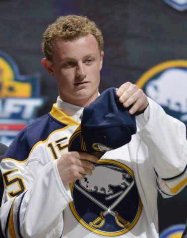 Jack Eichel putting on Sabres cap after being drafted.