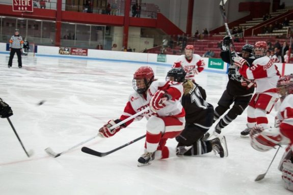 Boston, March 1, 2014 -- Boston University women's hockey defense Kaleigh Fratkin, center, and Providence College women's hockey forward Janine Weber, center right, play during the East Quarterfinals. The two may be teammates next season in NY. Photograph by Carolyn Bick. © Carolyn Bick/BUNS 2014.