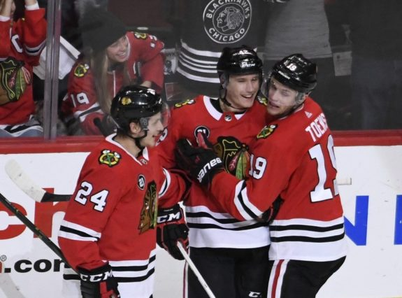 Chicago Blackhawks Gustav Forsling, center, celebrates with Dominik Kahun and Jonathan Toews