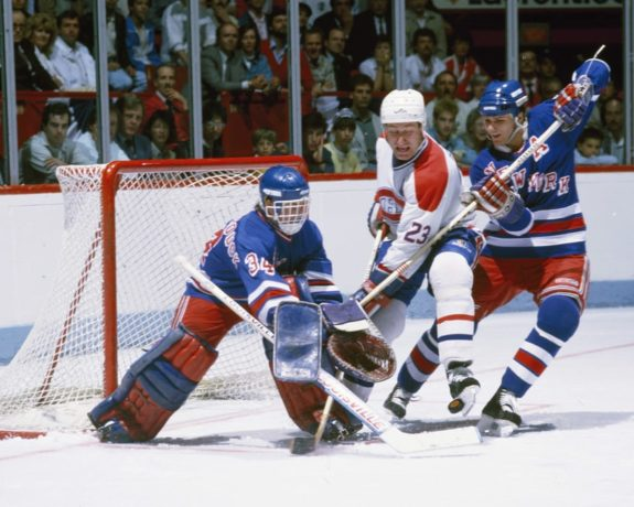 John Vanbiesbrouck pokes the puck away from Bob Gainey