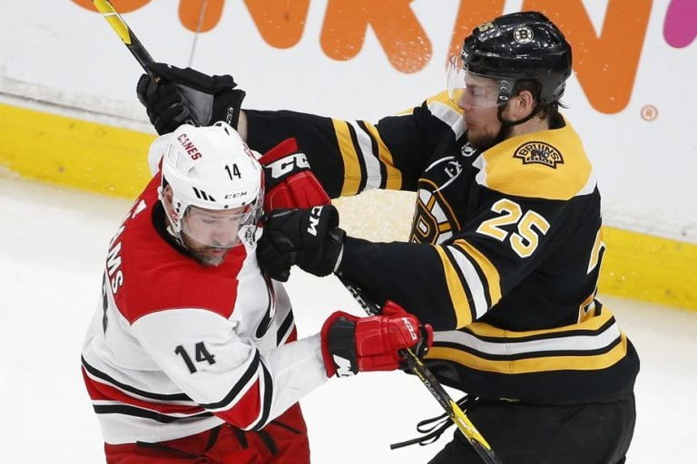 Boston Bruins defenseman Brandon Carlo (25) hits Carolina Hurricanes right wing Justin Williams