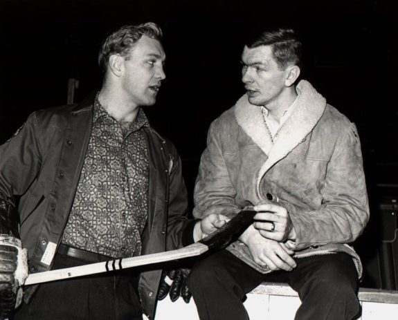 Bobby Hull #9 holds a hockey stick as he talks to teammate Stan Mikita
