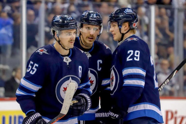 Mark Scheifele #55, Blake Wheeler #26 and Patrik Laine #29 of the Winnipeg Jets