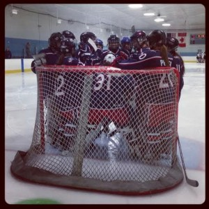 Ohio AAA Blue Jackets Girls gather round the net for a pregame meeting. (Photo Credit: Elaine Shircliff)