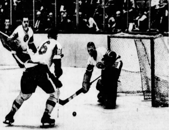 Pittsburgh goalie Don Caley prepares to clear a Springfield shot with the help of team mate Ted Taylor (16)