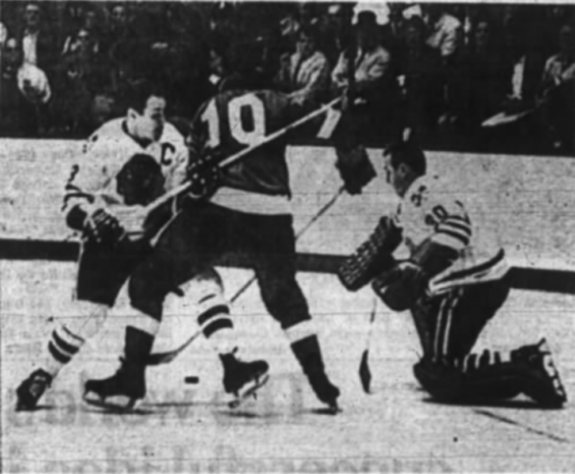 Detroit's Alex Delvecchio is tied up by Hawks' Pierre Pilote in last night's game.